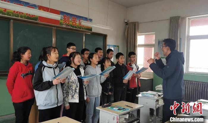 静乐县丰润中学音乐教师李晓斌正在给学生上音乐课。 杨杰英 摄