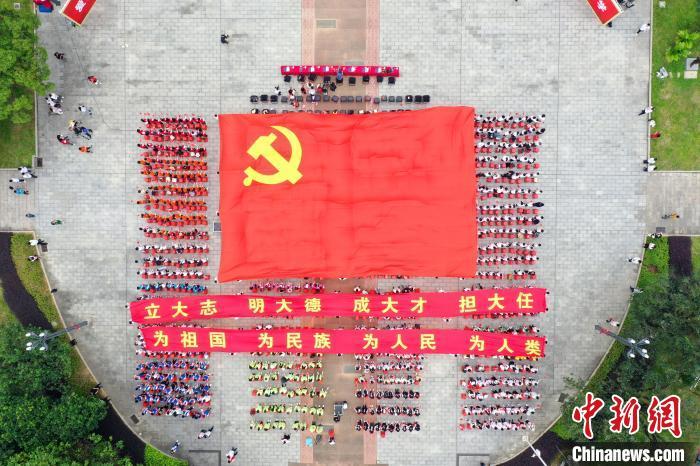 大学生展开巨幅党旗献礼党的百年华诞。 广西大学团委供图 摄