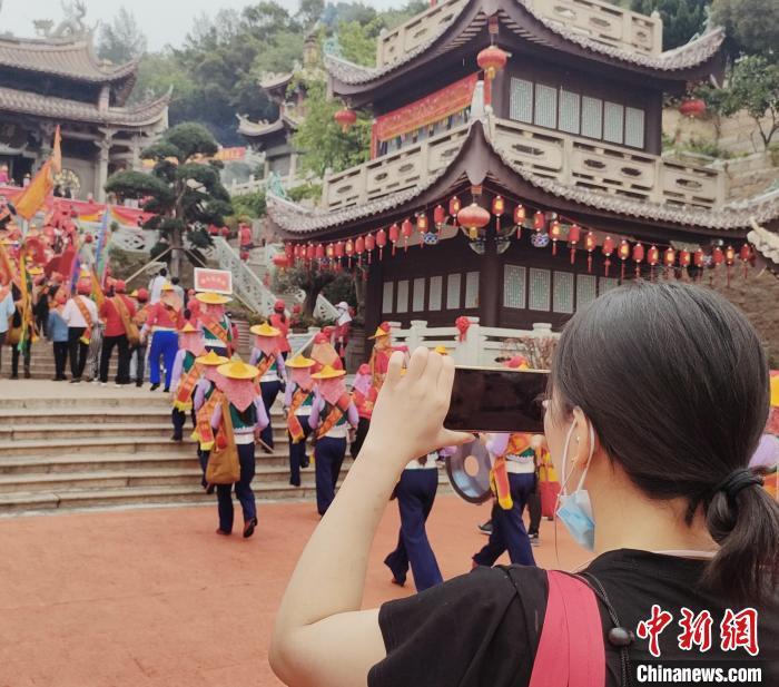 独具民族特色的进香人潮吸引游客驻足拍照。 高亚成 摄