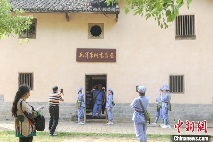 4月24日,身着红军装的游客在江西省瑞金市叶坪革命旧址群的毛泽东同志旧居门口合影留念。(资料图) 刘力鑫 摄